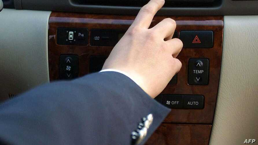 FILE - A salesman displays the latest built-in navigation system installed in a car in Beijing.