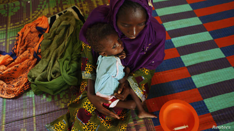 Bonko Diawara holds her 17-month-old daughter, Diarra Yattibere, as she recovers from malnutrition, at a nutrition center at Selibaby's hospital, in the Guidimakha region, Mauritania, June 2012.