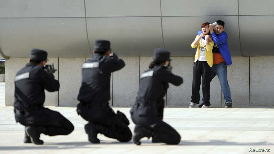Police officers take aim with their weapons at a man playing the role of an attacker as he holds a woman hostage during an anti-terrorism drill at a railway station in Zhengzhou, China, May 7, 2014.