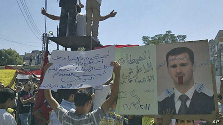 """The banners read """"The deaf and the blind devil"""" (l) and """"Step down devil"""" (c), as people protest against Syrian President Bashar al-Assad after Friday prayers in the city of Homs, September 16, 2011."""