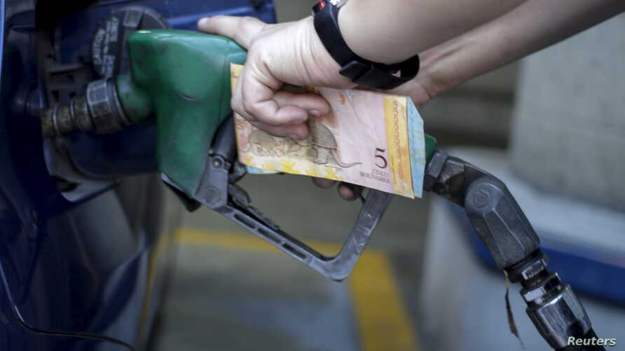 A worker pumps gas into a vehicle at a gas station belonging to Venezuela's state oil company PDVSA, as she holds bolivar notes, in Caracas, Feb. 13, 2016. Venezuela has the world's cheapest gasoline.