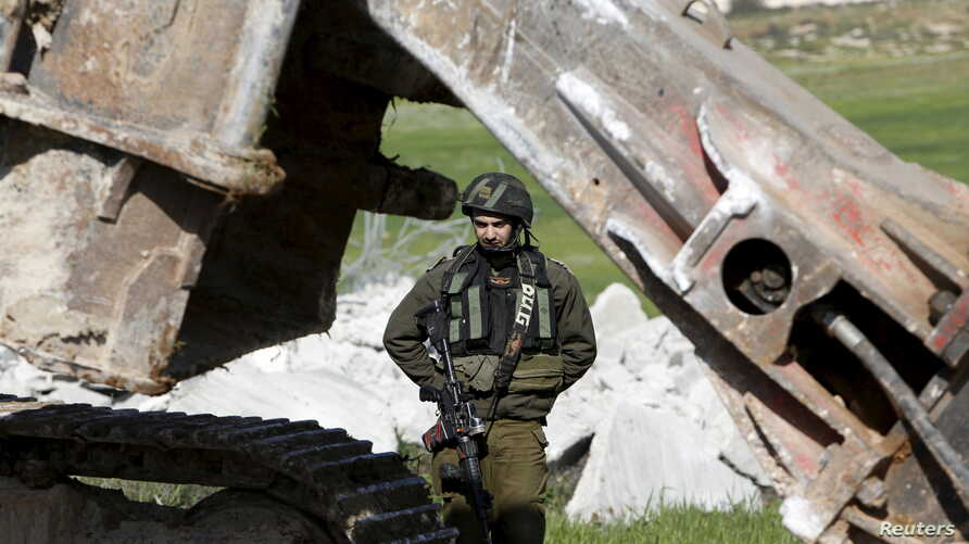 An Israeli soldier stands guard during the demolition of a Palestinian house at the order of the Israeli army, in the West Bank town of Dura, south of Hebron January 20, 2016.