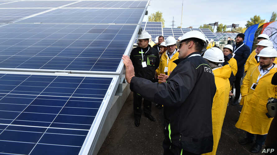 Visitors examine solar panels during the official opening ceremony of the new one-megawatt power plant next to the now sealed Chernobyl nuclear plant in Chernobyl, Ukraine, Oct. 5, 2018.