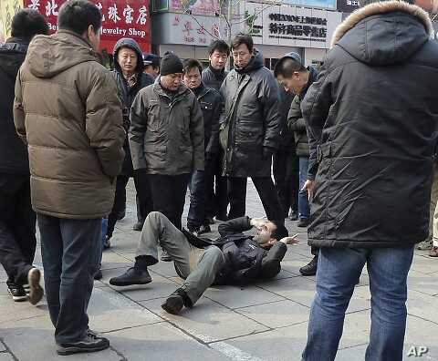 Unidentified men surround a foreign journalist who was pushed to the ground on Wangfujing Street after calls for a anti-government rally in  Beijing, Feb. 27, 2011