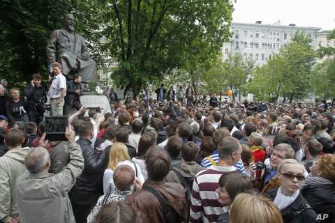 Russian opposition protesters gather near the monument of Kazakh poet Abai Kunanbaev in the opposition camp at the Chistiye Prudy, or Clean Ponds, where they vowed to continue the roving protest in Moscow, Russia, May 13, 2012.