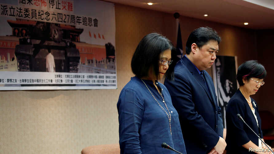 Wu'er Kaixi (C), one of the most charismatic student leaders of Beijing's 1989 pro-democracy movement, observes a minute of silence during Taiwanese lawmakers commemorate human rights meeting ahead of China's June 4 Tiananmen anniversary, at the Legi