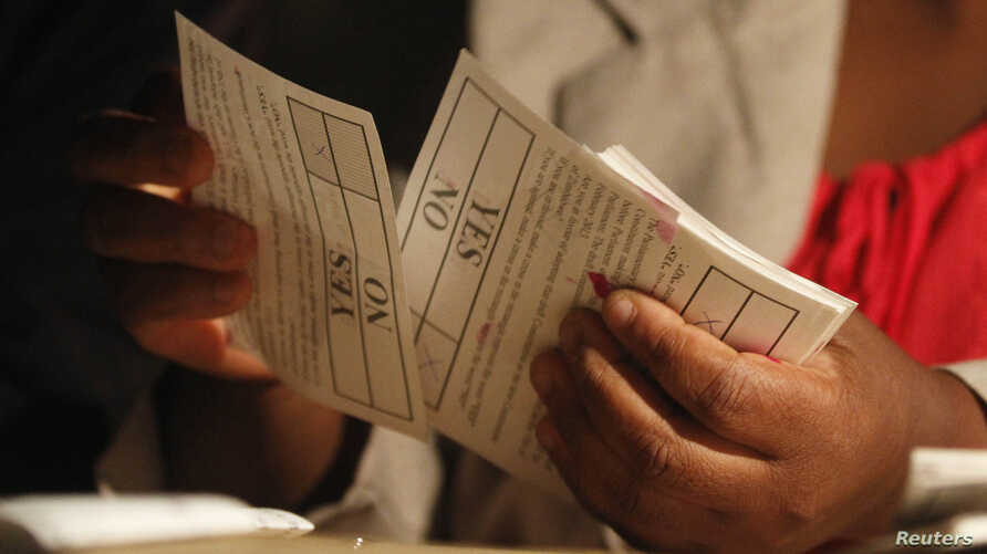 A Zimbabwean election official counts ballot papers after the close of voting on a referendum to approve a new constitution, in Harare, March 16, 2013.