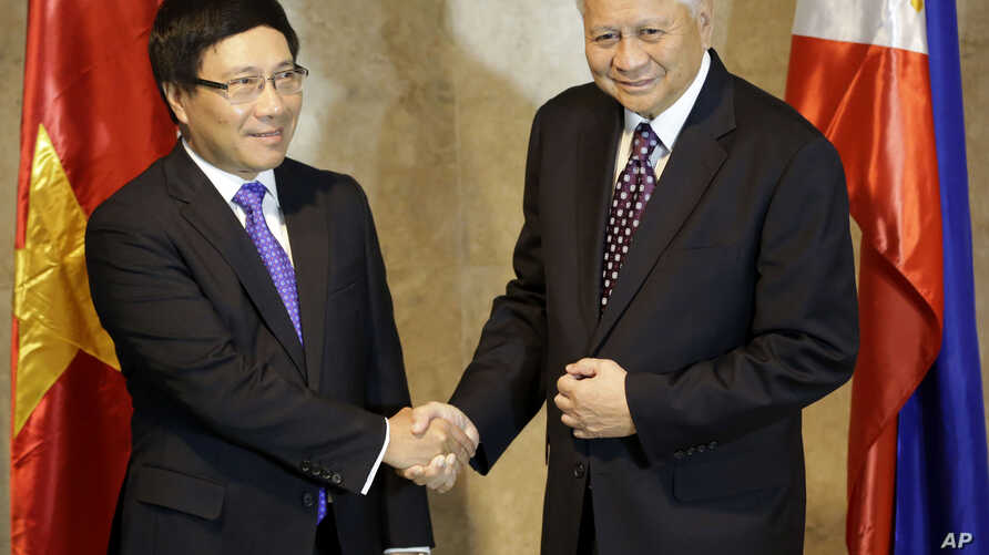 Philippine Foreign Affairs Secretary Albert Del Rosario, right, welcomes Vietnamese Foreign Minister Pham Binh Minh for their 7th Meeting of the Philippines-Vietnam Joint Commission for Bilateral Cooperation (JCBC) in Manila, Philippines, Aug. 1, 201