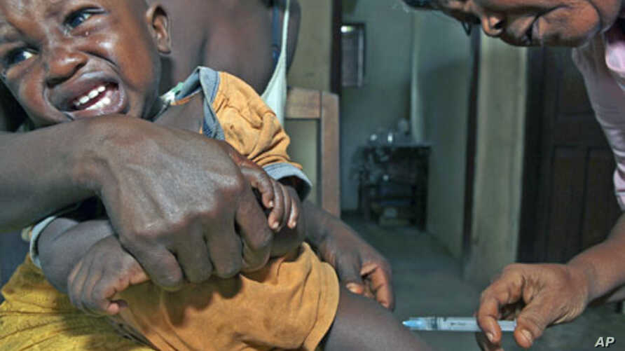 A Sierra Leonean maternal and child health aide administers a vaccine to a child in the village of Sembehun, outside the town of Bo, in the southeast region of the West African country, May 2011