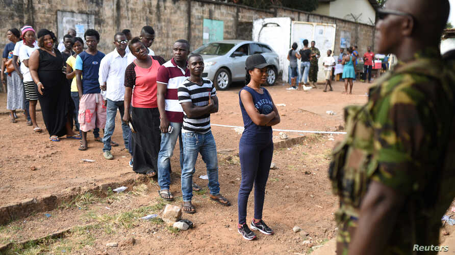 A member of the military stands guard as people queue to cast their votes during a presidential run-off in Freetown, Sierra Leone, March 31, 2018