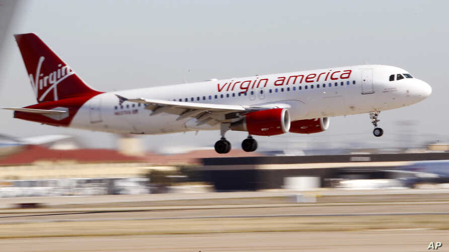 FILE - A Virgin America's flight between Los Angeles and Dallas is seen coming in for a landing at Dallas Fort Worth International Airport in Grapevine, Texas, Dec. 1, 2010. Alaska Air Group Inc. is eyeing to buy Virgin America in a deal valued at $4
