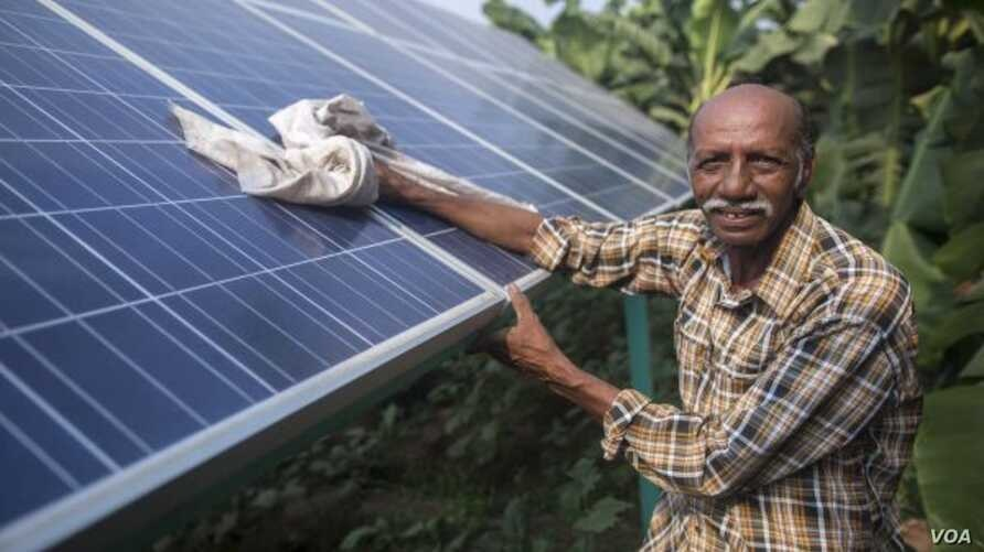Ramanbhai Parmar, has become the first farmer to sell energy back to the power grid from the solar panels that drive his water pump in Anand district, Gujrat, India, June 8, 2015. (International Water Management Institute photo, Prashanth Vishwanatha
