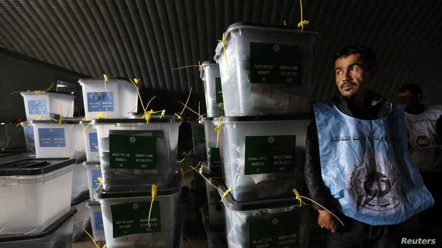 An Afghan election worker stands next to ballot boxes at a counting centre in Kabul. A bigger-than-expected turnout in Afghanistan's presidential election and the Taliban's failure to significantly disrupt the vote has raised questions about the capa