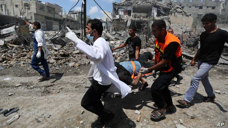 Palestinian medics carry a man injured in Gaza City's Shijaiyah neighborhood that came under fire as Israel widened its ground offensive against Hamas in the northern Gaza Strip, July 20, 2014.