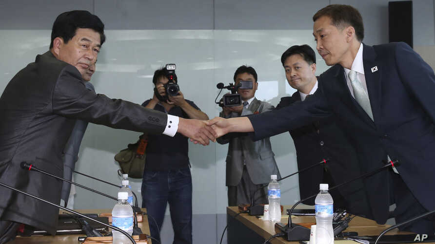 Kim Kiwoong, right, the head of South Korea's working-level delegation, shakes hands with his North Korean counterpart Park Chol Su, left, before their meeting at Kaesong Industrial District Management Committee in Kaesong, North Korea, August 14, 20