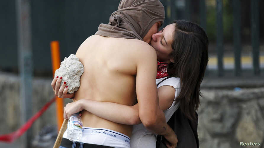 Anti-government protesters kiss during protest against Venezuela's President Nicolas Maduro's government, Caracas, March 22, 2014.