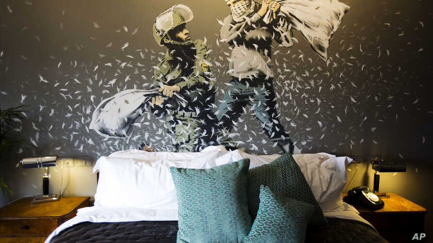 """A Banksy wall painting showing Israeli border policeman and Palestinian in a pillow fight is seen in one of the rooms of the """"The Walled Off Hotel"""" in the West Bank city of Bethlehem, March 3, 2017."""