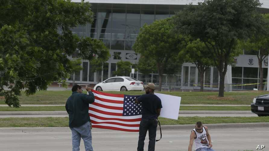 Men hold a sign and a U.S. flag across the street from the Curtis Culwell Center, where two men opened fire at an event soliciting cartoons of the Prophet Mohammad, in Garland, Texas, May 5, 2015.