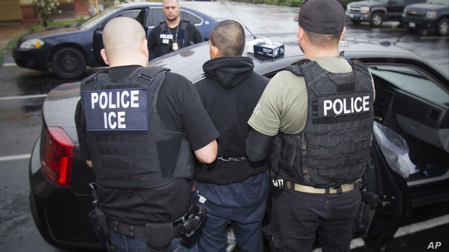 FILE - In this photo released by U.S. Immigration and Customs Enforcement, foreign nationals are arrested during a raid aimed at immigration fugitives, re-entrants and at-large criminal aliens in Los Angeles, Feb. 7, 2017.