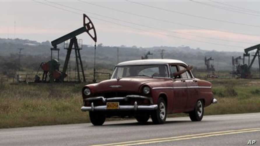 In this photo taken on Jan. 12, 2012, a man waves from his classic car as he drives by oscillating oil pumps operated by the state oil company Cuba Petroleos, Cupet, in Santa Cruz del Norte, Cuba.  A Chinese-built oil rig has arrived to Cuba in Janua