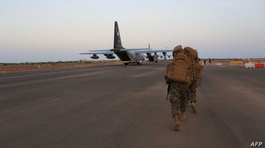 FILE - In this image released by the U.S. Department of Defense, U.S. Marines and sailors prepare to board a KC-130J Marine Super Hercules at Camp Lemonnier, Djibouti.