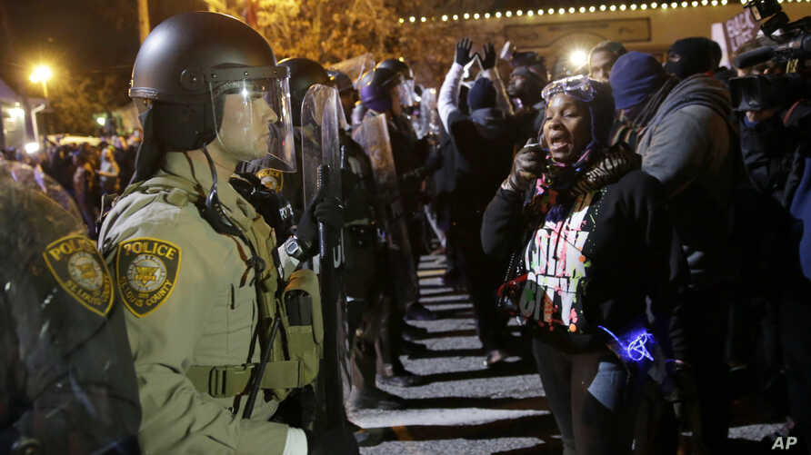 Police officers stand guard as protesters react to the announcement of the grand jury decision not to indict police officer Darren Wilson in the fatal shooting of Michael Brown, an unarmed black 18-year-old, Nov. 24, 2014, in Ferguson, Missouri.