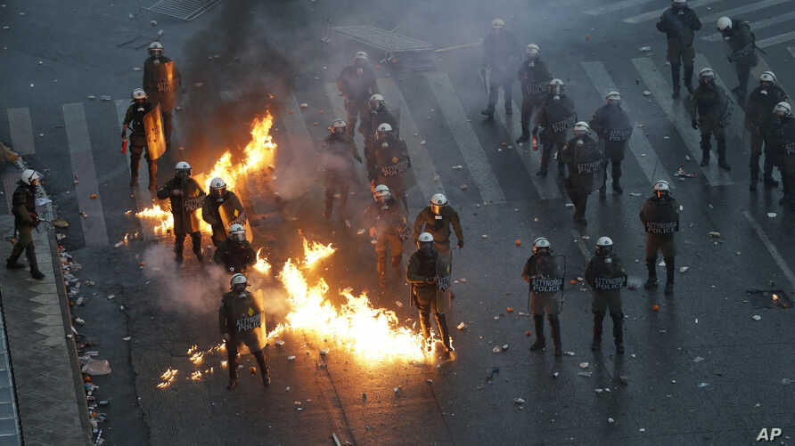 A molotov cocktail explodes next to Greek riot police during clashes after a rally in Athens, Jan. 20, 2019.