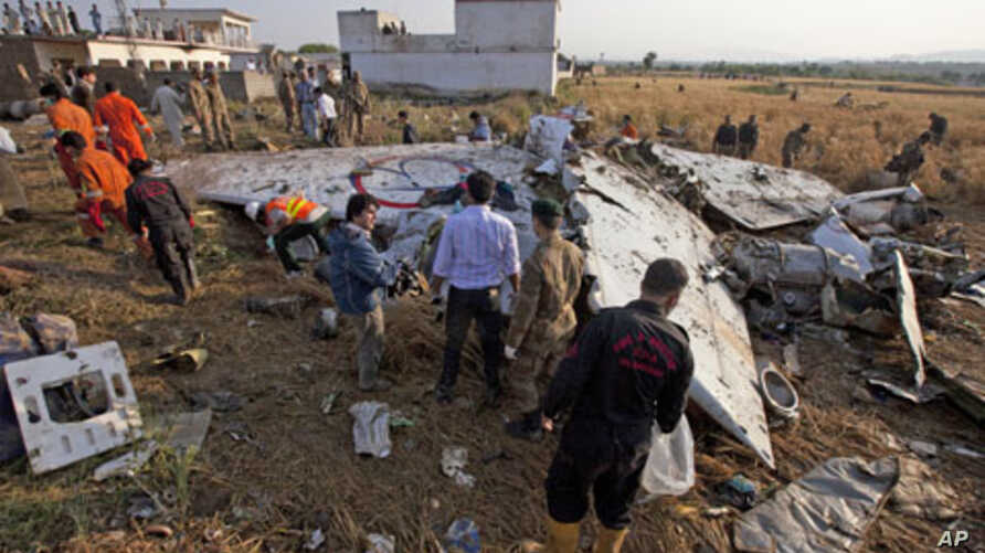 Paramilitary soldiers and members of the media gather near the wreckage of a Boeing 737 airliner that crashed in Islamabad, April 21, 2012.