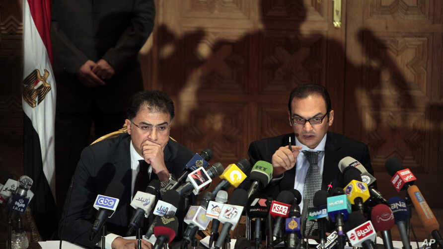 Egyptian investigative judges Sameh Abu Zeid, right, and Ashraf el-Ashmawi, who are  investigating  the case of foreign funding of NGOs, talk during a press conference at the Ministry of Justice in Cairo, Egypt, Feb. 8, 2012.