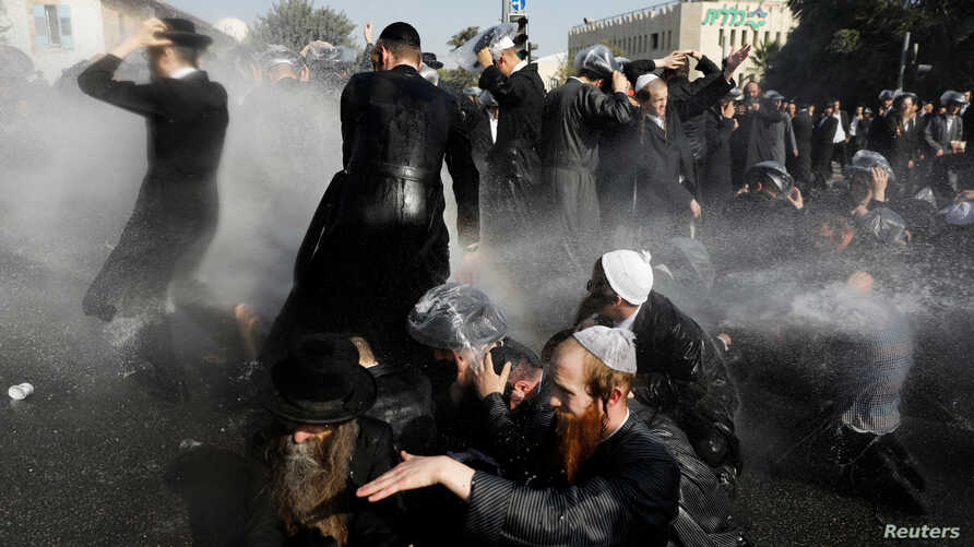 Israeli ultra-Orthodox Jewish men are sprayed with water canons during clashes with police at a protest against the detention of a member of their community who refuses to serve in the Israeli army, in Jerusalem, Israel, Sept. 17, 2017.
