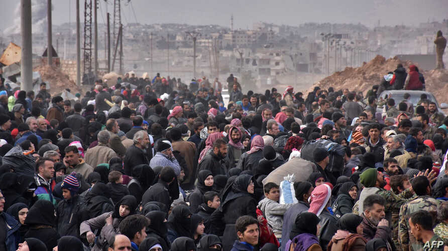 Syrian families, fleeing from various eastern districts of Aleppo, queue to get onto governmental buses, Nov. 29, 2016 in the government-held eastern neighbourhood of Jabal Badro, before heading to government-controlled western Aleppo.