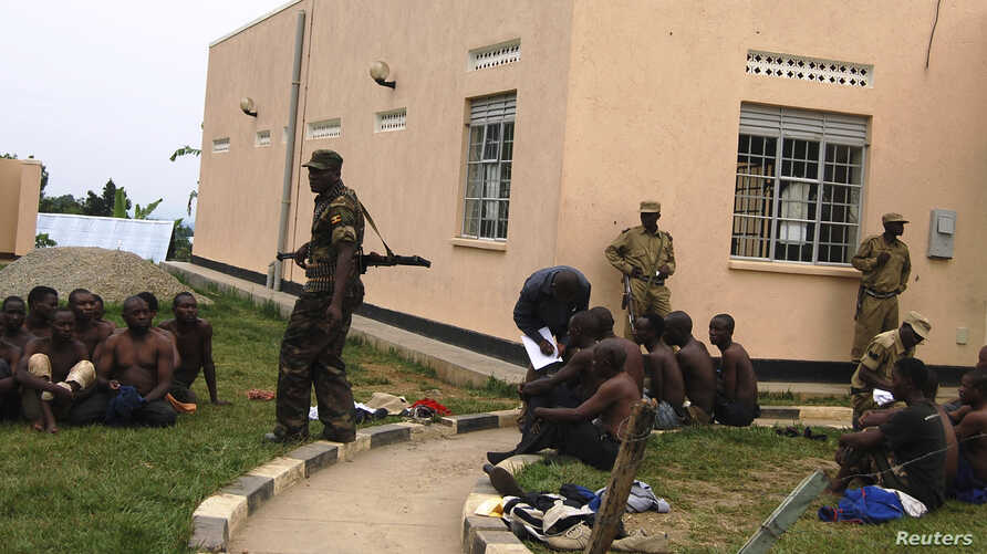 Uganda People's Defense Forces soldiers detain men suspected to be militia members after unidentified gunmen attacked Bundibugyo town in Western Uganda, July 6, 2014.