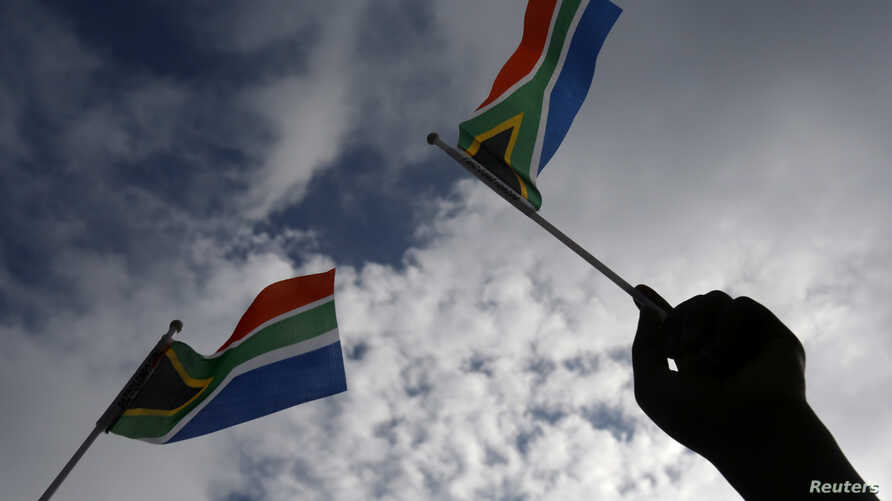 FILE - Flags of South Africa wave in Pretoria, Dec. 11, 2013. South Africans are outraged over a video featuring a racist rant.