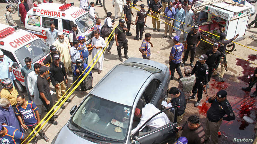 Police officers inspect a car after unidentified gunmen carried an attack on a prominent Pakistani cleric in Karachi, Pakistan, March 22, 2019.