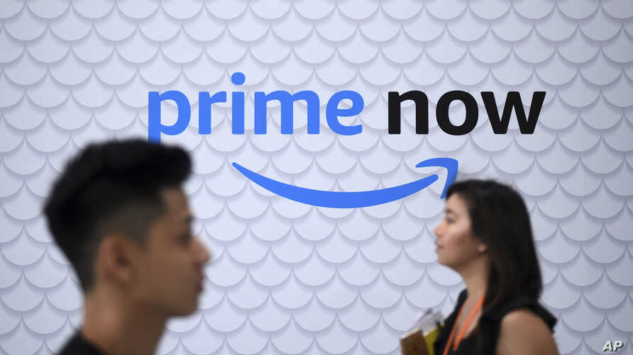 Staff walk in front of a sign at the newly opened Amazon Prime Now facility in Singapore, July 27, 2017,
