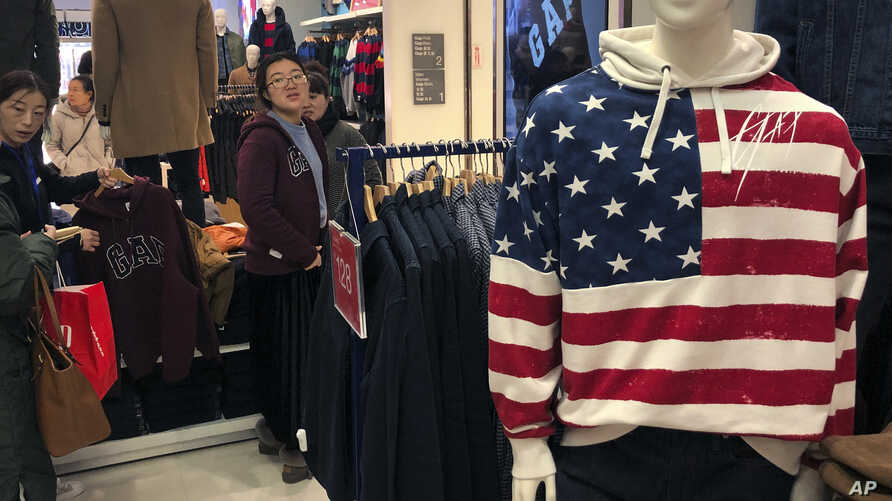 FILE - A woman tries out a sweater at U.S. retailer GAP's flagship store in Beijing, Jan. 10, 2019.