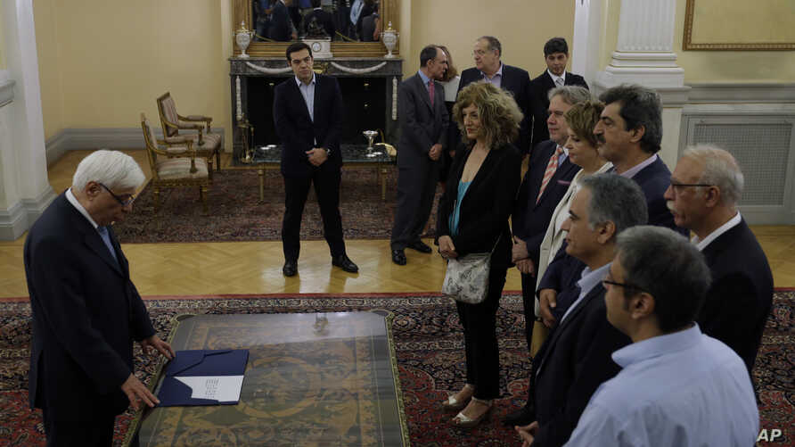 Greek President Prokopis Pavlopoulos, left, administers the secular oath to the new members of the government during a swearing in ceremony at the Presidential Palace in Athens, July 18, 2015.
