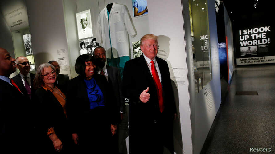U.S. President Donald Trump (R) gives the thumb-up at the Dr. Ben Carson (2ndR) exhibit while visiting the National Museum of African American History and Culture in Washington, Feb. 21, 2017.