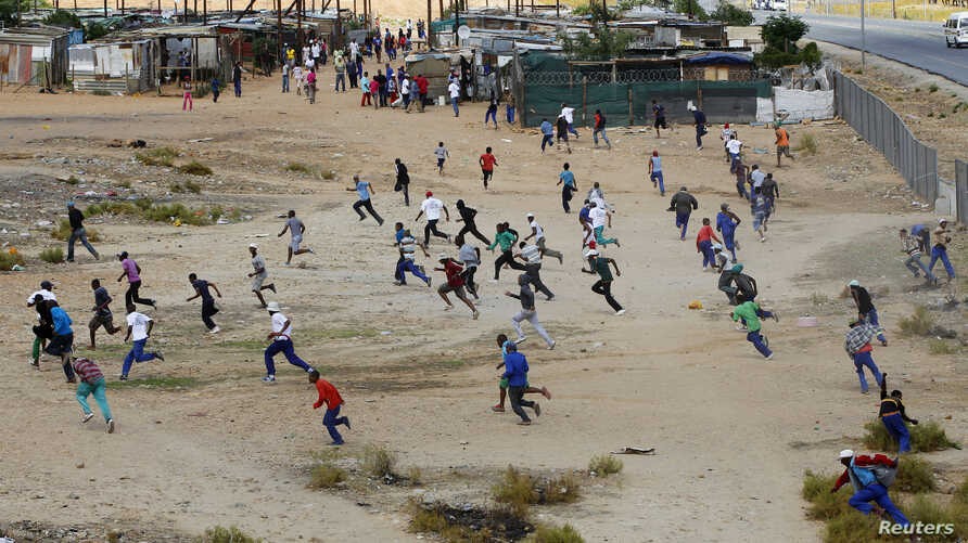 Protesters flee as police open fire during a farm workers strike at De Doorns, on the N1 highway linking Cape Town and Johannesburg, January 9, 2013.