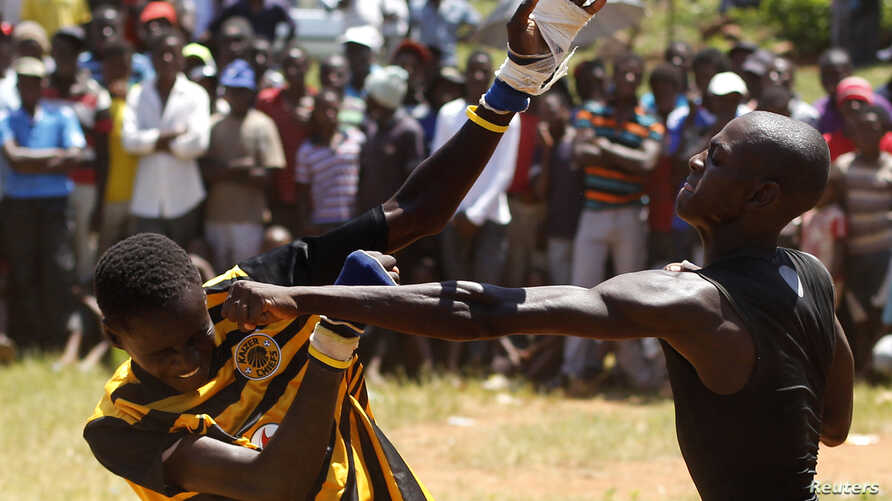 FILE - Fist fighters battle during the Musangwe, an age old tradition where men and boys display their fighting skills, at Gaba Village in Limpopo province, South Africa.