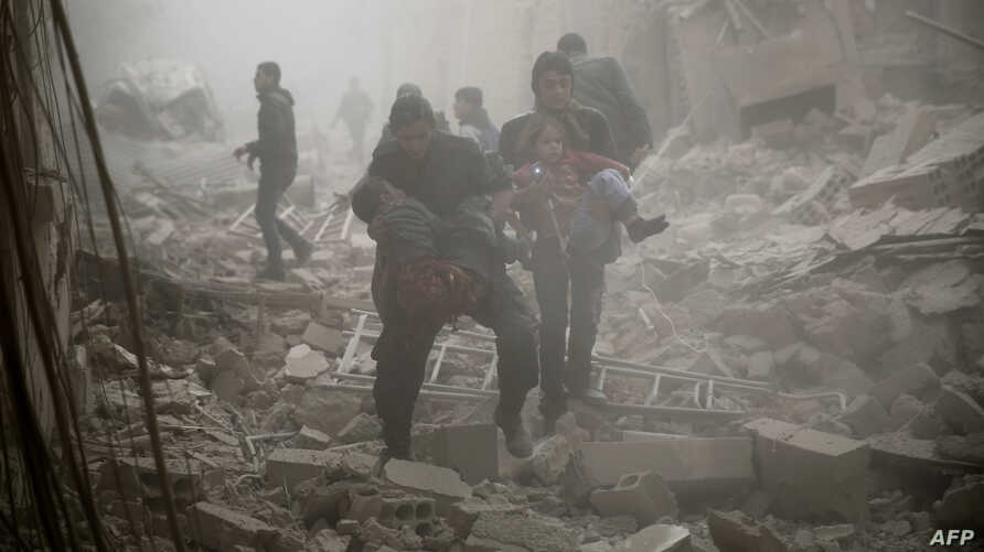 Syrians evacuate victims following air strikes on the town of Douma in the eastern Ghouta region, a rebel stronghold east of the capital Damascus, Dec. 13, 2015.