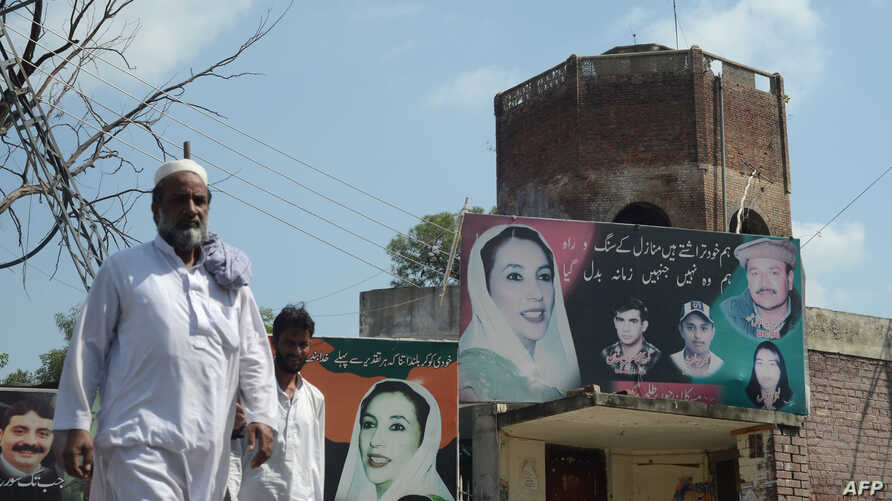 FILE - Pedestrians walk past the assassination site of opposition leader Benazir Bhutto in Rawalpindi.