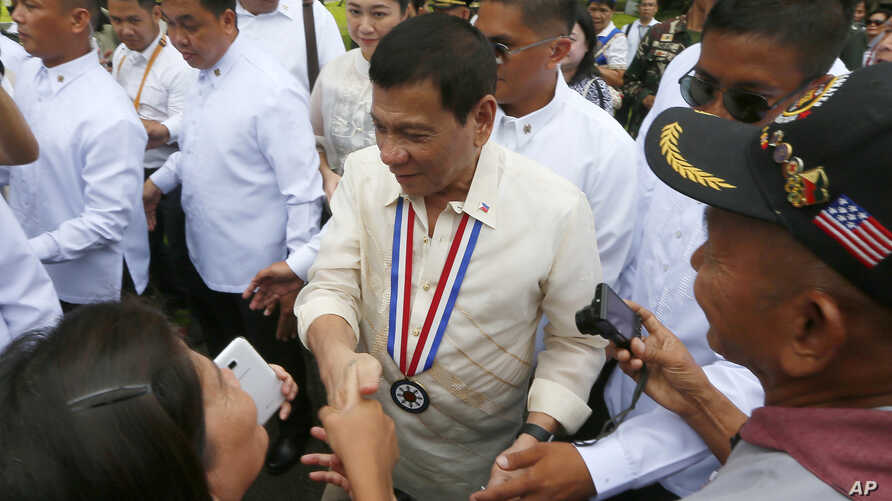 Philippine President Rodrigo Duterte poses is greeted by supporters following a wreath-laying ceremony in observance of National Heroes Day Monday, Aug. 29, 2016 at the Heroes Cemetery in suburban Taguig city east of Manila, Philippines.