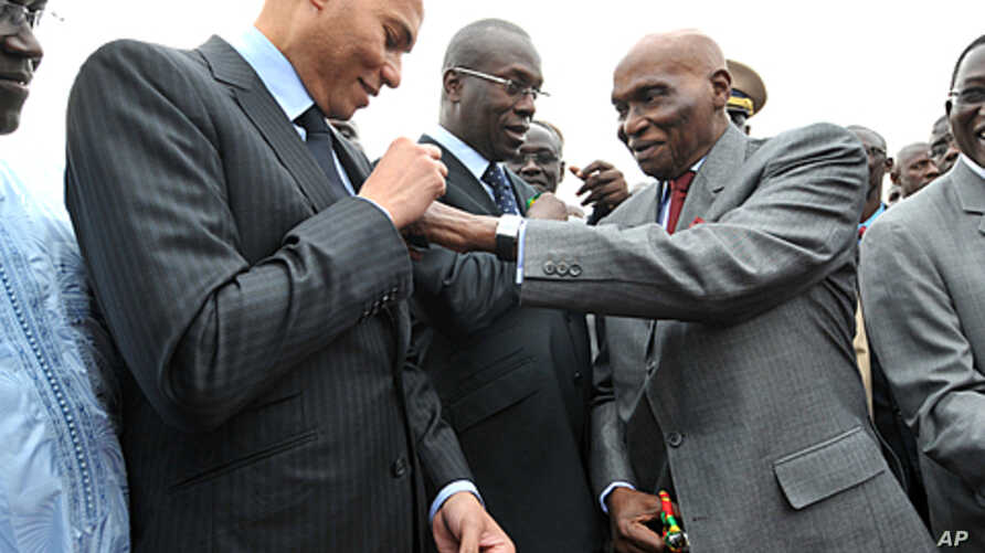 Senegalese President Abdoulaye Wade (R) adjusts a ribbon on his son's jacket, Karim Wade (C), during a ceremony to mark the arrival of two Senegal airlines airbus on January 19, 2011 in Dakar