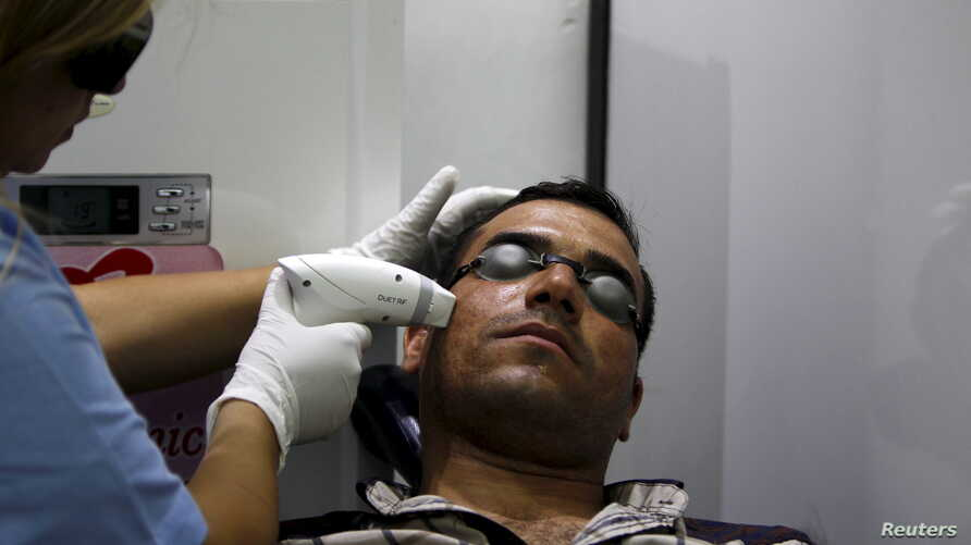 """FILE - A man has acne removed from his face with a laser at a clinic in Baghdad, Iraq, June 2, 2015. Researchers have found that cream personalized with a person's own """"good"""" bacteria may help ward off """"bad"""" bacteria."""