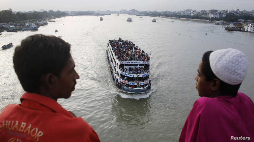 An overcrowded passenger boat navigates through Buriganga River as people watch from a bridge in Dhaka, Bangladesh, July 27, 2014.
