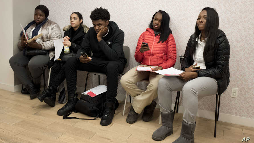 FILE - Young job seekers wait to meet with recruiters during a job fair hosted by the Gregory Jackson Center for Brownsville, in the Brooklyn borough of New York.