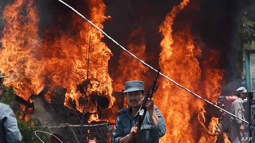 An Afghan policeman stands guard as smoke and flames rise from the site of a huge blast struck near the entrance of Kabul's international airport, in Kabul on August 10, 2015.