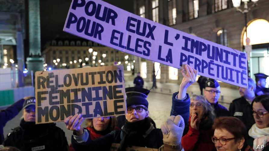 A feminist activist holds placards near the Justice ministry during a protest calling to change French statutory rape laws after a man was acquitted of raping an 11-year-old, in Paris, Nov. 14, 2017.