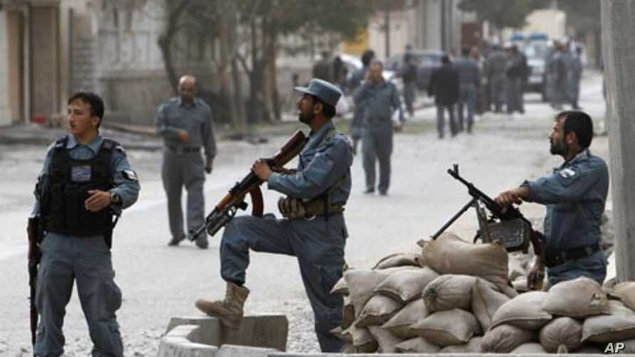 Afghan policemen keep watch at the site of a suicide attack in Kabul September 13, 2011.